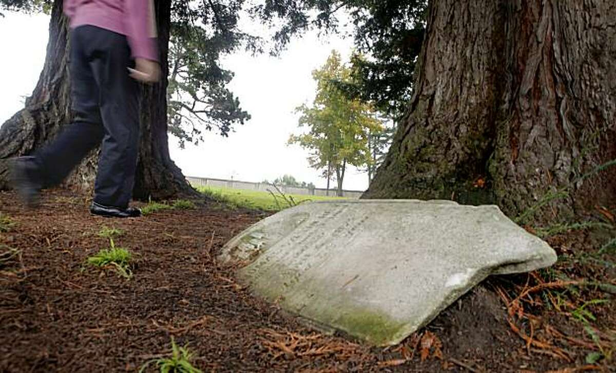 """Gaye Lenahan, a docent at the Mountain View Cemetery walks through the """"Stranger's Plot"""", which is the Bay Areas' own Potter's Field, December 13, 2010, in Oakland, Calif. The sloping green field is where more than 500 poor people, criminals, suicides and infants were buried years ago."""