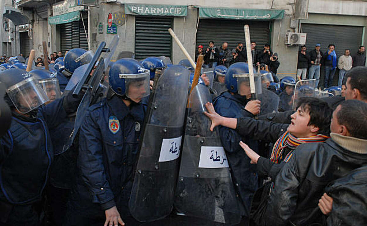 Protestors pushes riot policemen during a demonstration in Algiers Saturday Jan. 22, 2011. About 300 people has defied a ban to attempt to hold the demonstration but were confronted by dozens of police armed with batons, and tear gas. Several were injuredin the riots.