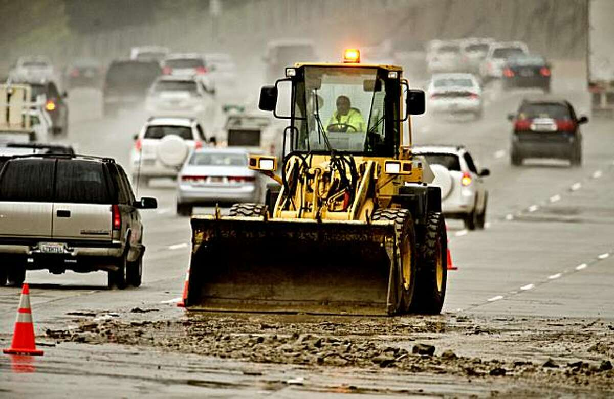 A Caltrans dozer operator scrapes mud off the right three lanes of the eastbound 91 freeway near Green River Rd. near Corona, Calif. Wednesday, Dec. 29, 2010. A mudslide on the eastbound side of the 91 freeway blocked blocked at least three lanes of the freeway for up to six hours, authorities said. (AP Photo/Orange County Register, Bruce Chambers) NO SALES; MAGS OUT; LOS ANGELES TIMES OUT