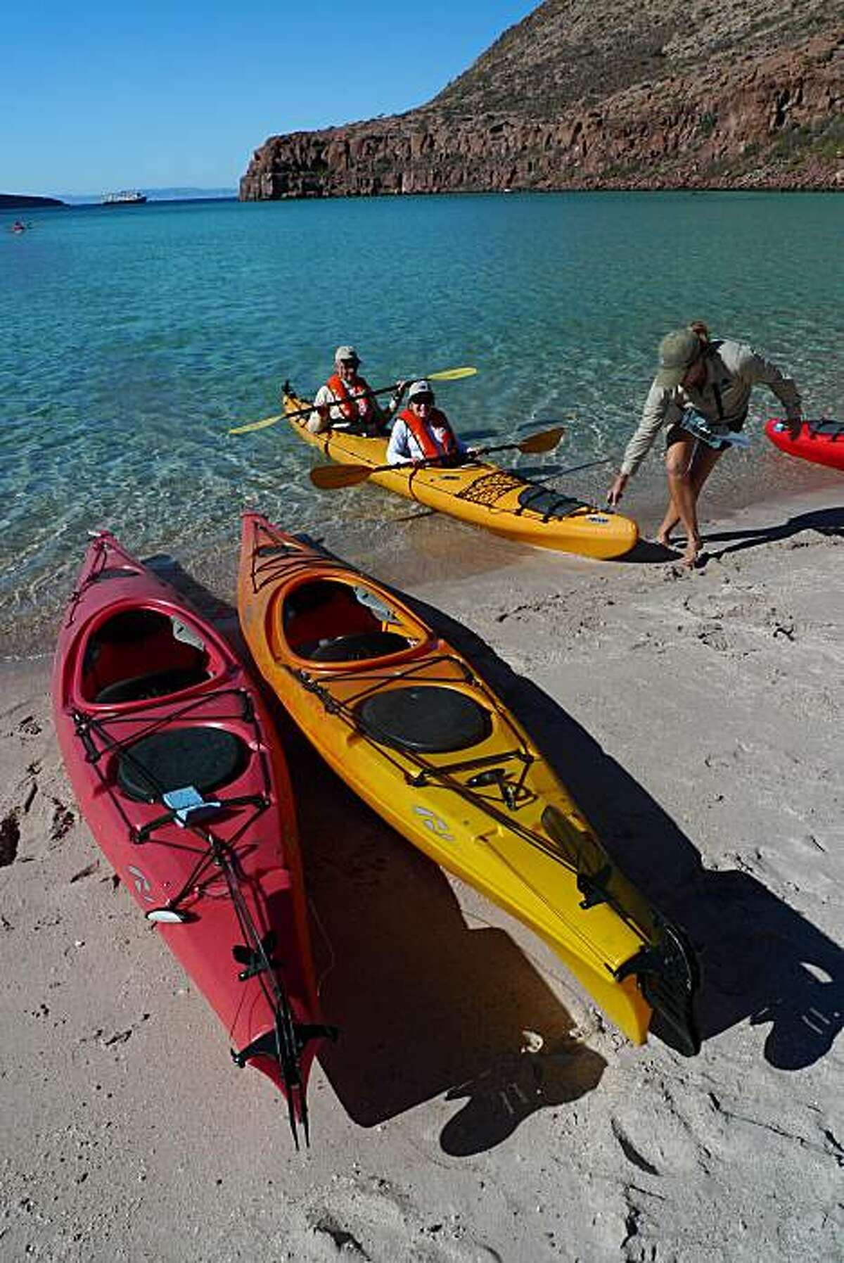 Passengers from the National Geographic Sea Bird land on the beach after kayaking around Ensenada Grande on Espiritu Santo island in the Sea of Cortez.