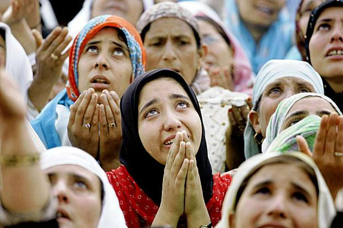 Kashmiri Muslim women pray as a head priest, unseen, displays a holy relic believed to be the hair from the beard of Prophet Mohammad, during special prayers at the Islamic festival of Shab-e-Meraj at the Hazratbal Shrine in Srinagar, India, Tuesday, July 21, 2009. Shab-e-Meraj is celebrated as the anniversary of Prophet Mohammad's ascent to heaven. (AP Photo/Mukhtar Khan)
