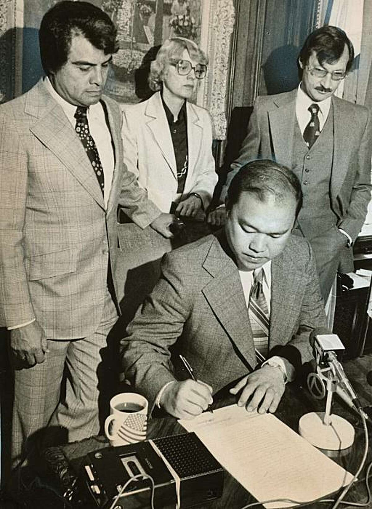 San Francisco Supervisor Gordon Lau, seated, signing the Rent Control Law, with Supervisors Bob Gonzales, left, Louise Renne, and Don Horanzy, in June 1979. Clem Albers/San Francisco Chronicle