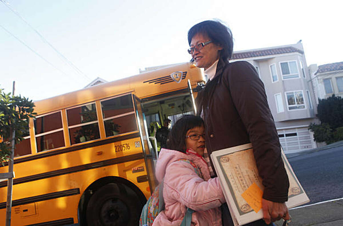 Lely Ma (right), Chinese librarian, gets a hug from Chloe Vuong (foreground left), 7, while greeting children as they disembark from a school bus as they arrive for school at Alice Fong Yu Elementary School on Tuesday, January 4, 2011 in San Francisco, Calif.
