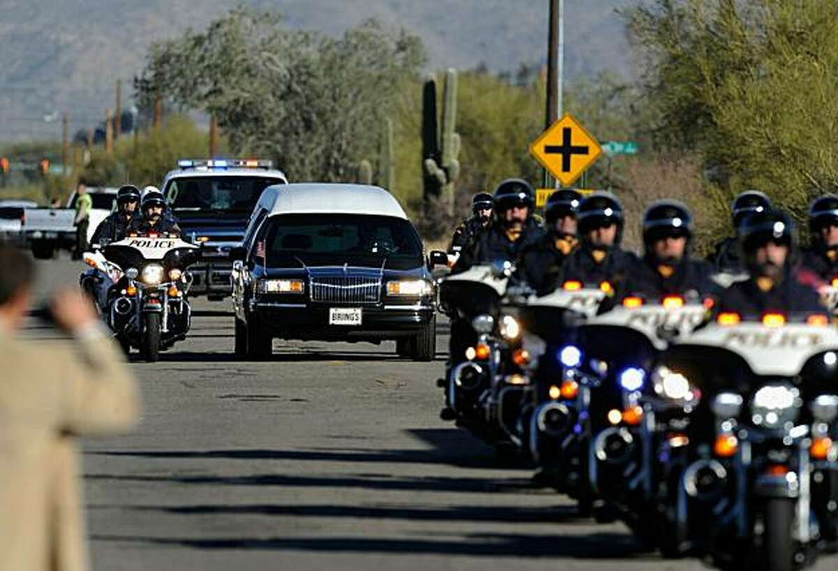 TUCSON, AZ - JANUARY 14: A hearse carrying the casket of US District Court Judge John Roll passes in front of St. Elizabeth Ann Seton church for a funeral service January 14, 2011 in Tucson, Arizona. Heavy security surrounds the funeral of Judge Roll, who was shot during the January 8, shooting rampage of Jared Lee Loughner at a political event in Tucson, Arizona
