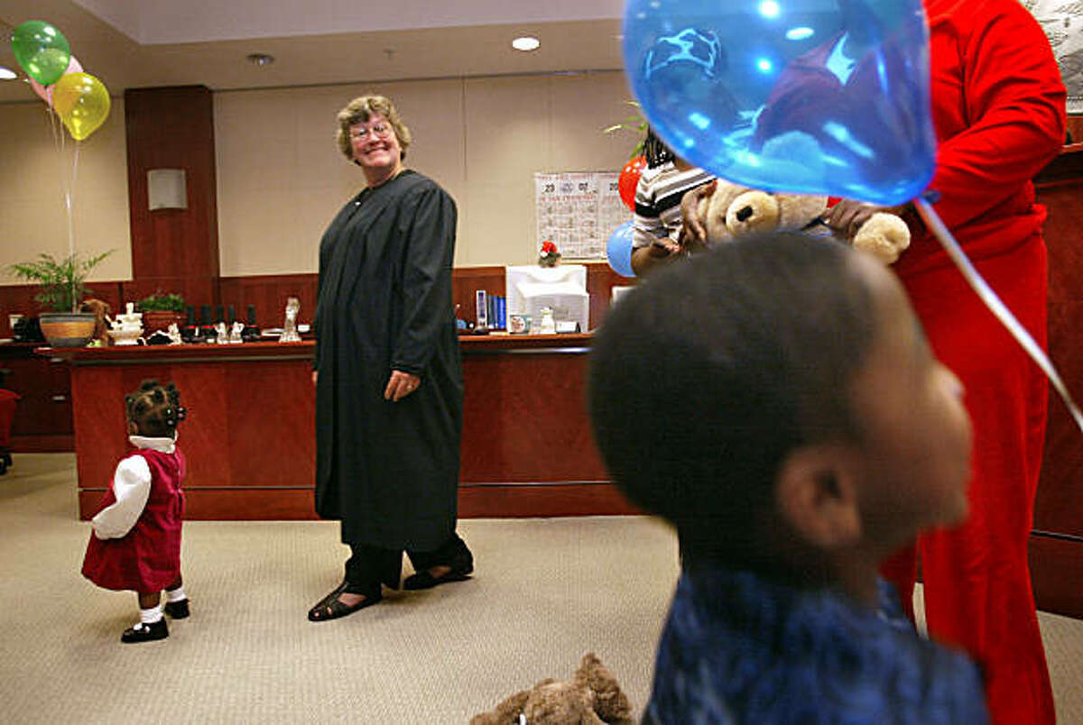 HITCHENS1-C-23NOV02-MT-DF Judge Donna Hitchens has helped alot of people to adopt children. She was in her office today, on her day off to hold a ceremony for the families who have adopted. She watches the kids play with balloons and teddy bears that she gave them. CHRONICLE PHOTO BY DEANNE FITZMAURICE