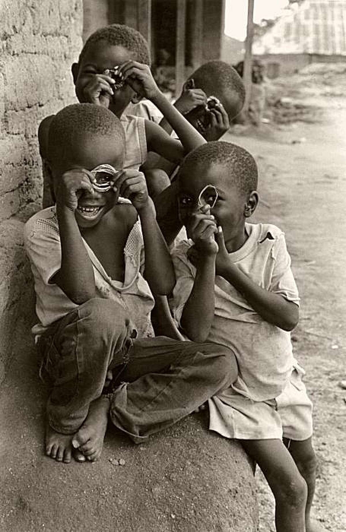 Children in Sierra Leone fashion their own camera lenses from weeds and mimic photographer Michael Katakis, 1988.