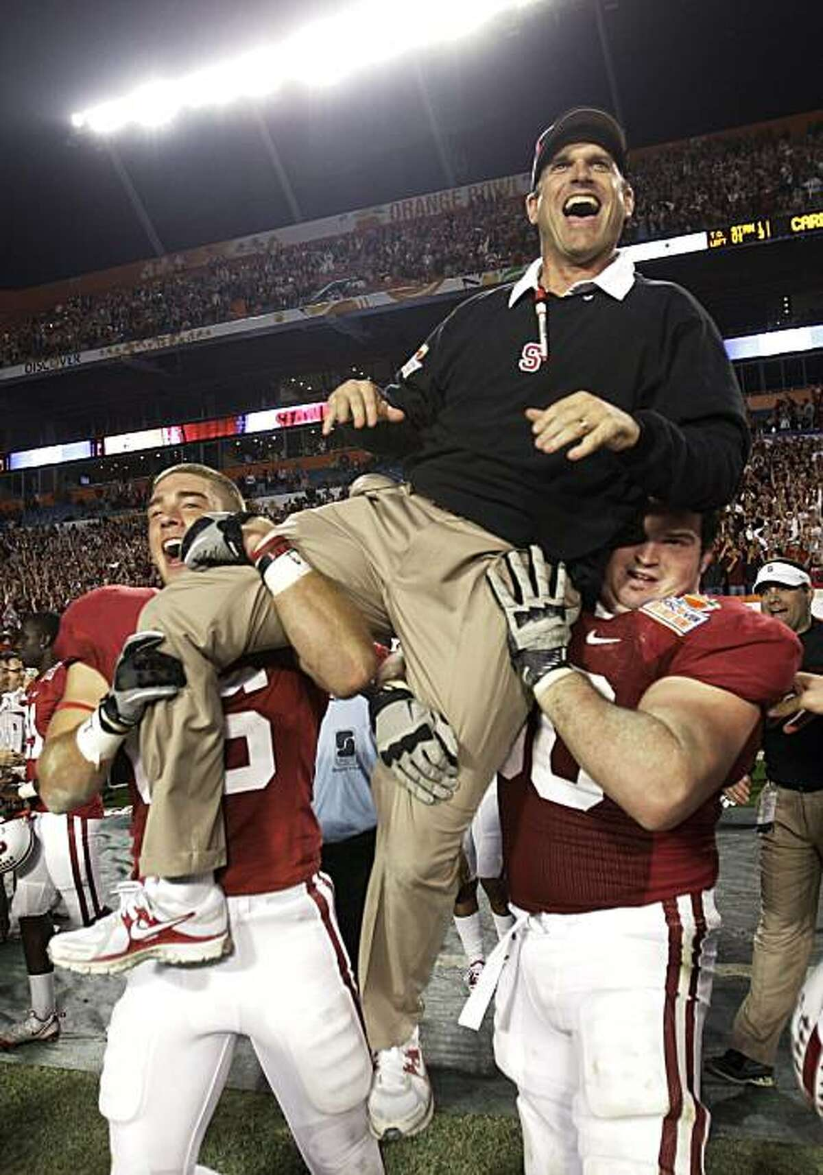 Stanford coach Jim Harbaugh is lifted by players after Stanford's 40-12 victory over Virginia Tech in the Orange Bowl NCAA college football game, Monday, Jan. 3, 2011, in Miami.