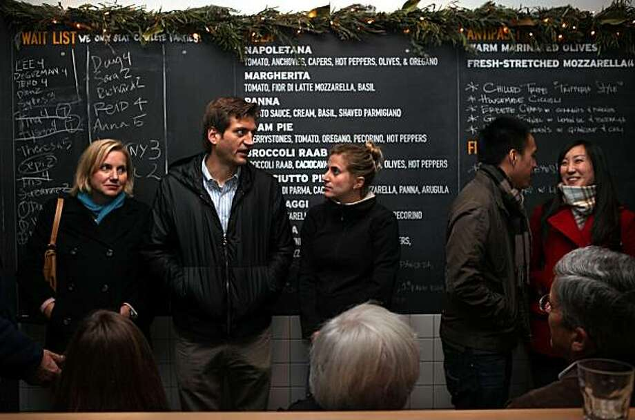 Theresa Vaughan (left) waits for a table at Pizzeria Delfina in San Francisco along with Andrew Skrip, Sara Claster, Arthur Che and Kathy Lee. Photo: Liz Hafalia, The Chronicle