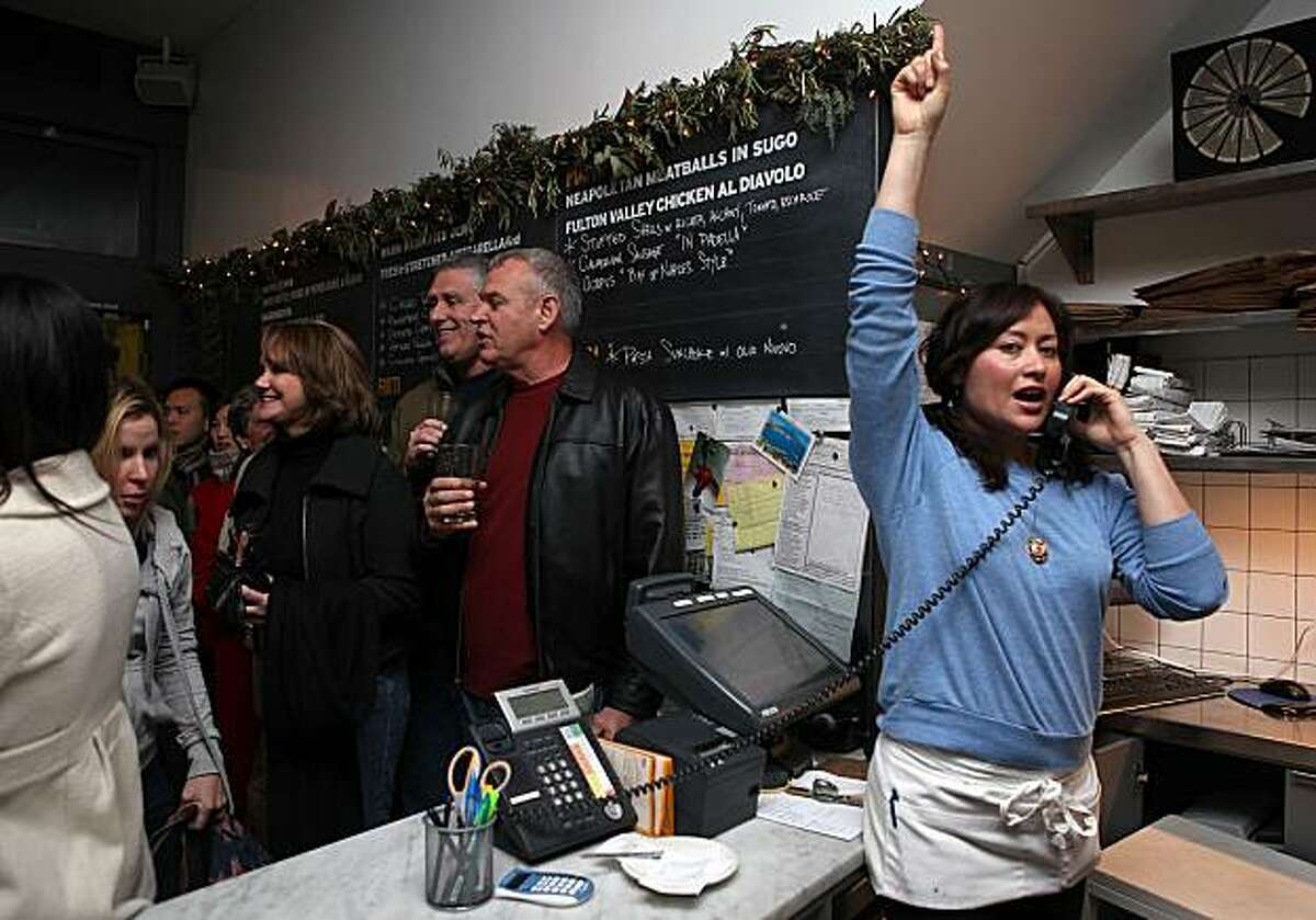Host Ivonne Melgar signaling the kitchen for a quote time as the dinner crowd waits in line behind her at Delfina's Pizzeria in San Francisco, Calif., on Thursday, December 30, 2010.