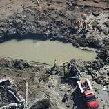 Emergency crews pump water from a crater in San Bruno, Calif. on Friday, Sept. 10, 2010 after a massive natural gas pipeline explosion destroyed dozens of homes Thursday night.