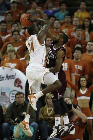 University of Texas guard J'Covan Brown drives to the goal against Texas A&M guard Dash Harris during the second half at the Frank Erwin Center in Austin, Texas, Wednesday, Jan. 11, 2012. The Longhorns won 61-51. JERRY LARA/glara@express-news.net Photo: JERRY LARA, Express-News / SAN ANTONIO EXPRESS-NEWS