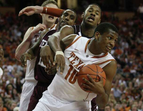 University of Texas forward Jonathan Holmes rebounds the ball under pressure from Texas A&M forward David Loubeau, left, and center Keith Davis during the second half at the Frank Erwin Center in Austin, Texas, Wednesday, Jan. 11, 2012. The Longhorns won 61-51. JERRY LARA/glara@express-news.net Photo: JERRY LARA, Express-News / SAN ANTONIO EXPRESS-NEWS
