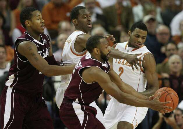 Texas A&M guard Dash Harris, front center, grabs the ball away from University of Texas guard, Sheldon McClellan, left, and forward Jaylen Bond, right, during the first half at the Frank Erwin Center in Austin, Texas, Wednesday, Jan. 11, 2012. On the left is teammate center Keith Davis. JERRY LARA/glara@express-news.net Photo: JERRY LARA, Express-News / SAN ANTONIO EXPRESS-NEWS