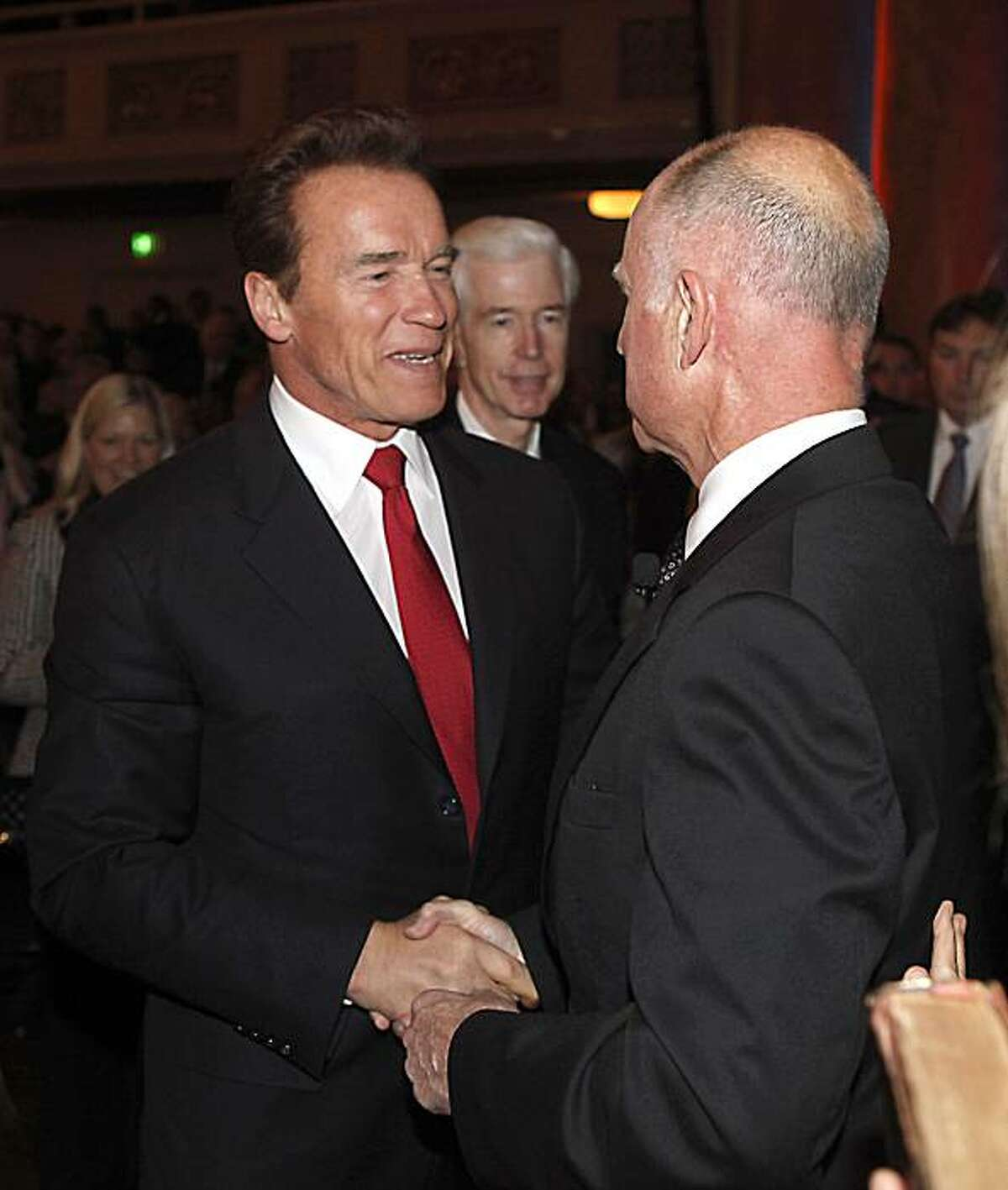 Outgoing Governor Arnold Schwarzenegger, left, congratulates his successor, Jerry Brown after Brown was sworn in as the 39th Governor of California in Sacramento, Calif. Monday, Jan. 3, 2011. Former Governor Gray Davis is seen in the center.