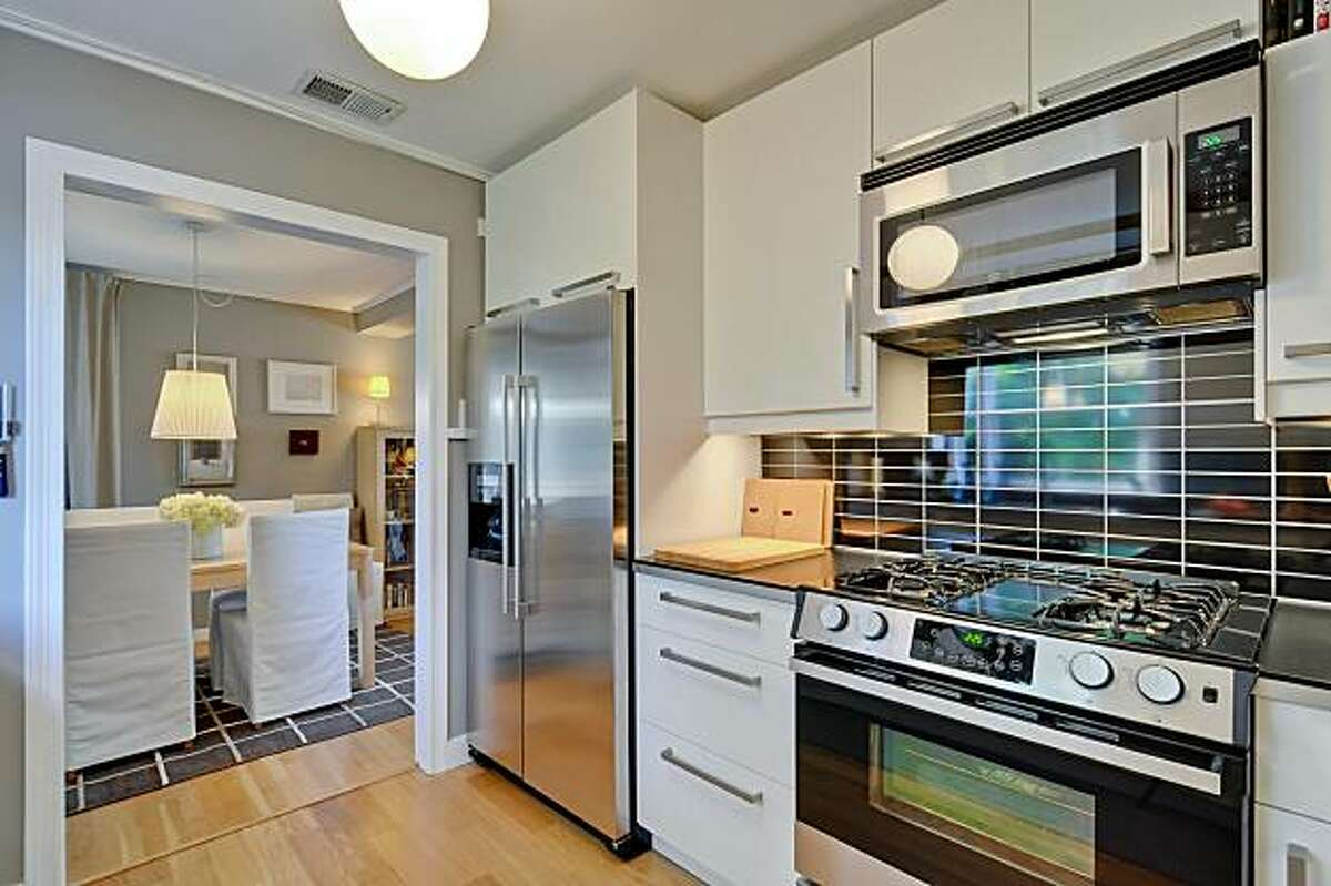 A sleek new kitchen features stainless steel appliances and a wide picture window above the sink. It opens to the formal dining room.