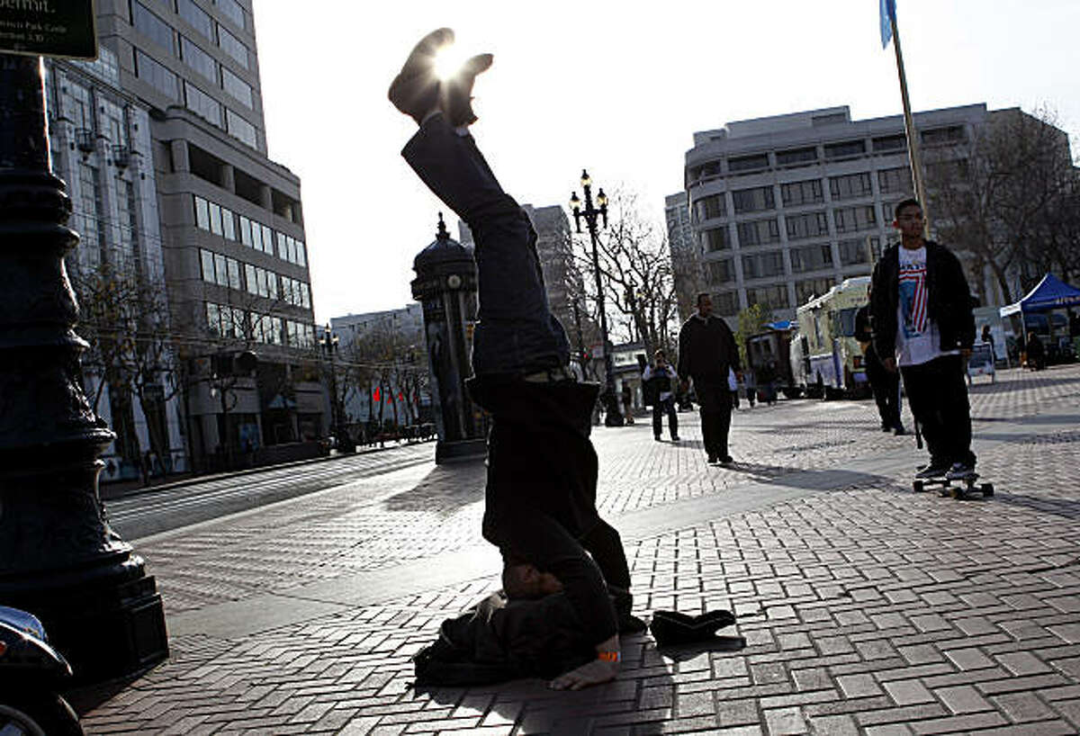 At the United Nations Plaza, a man does a head stand for money. A day in the life of the mid-Market Street area of San Francisco, Calif. Thursday December 16, 2010.