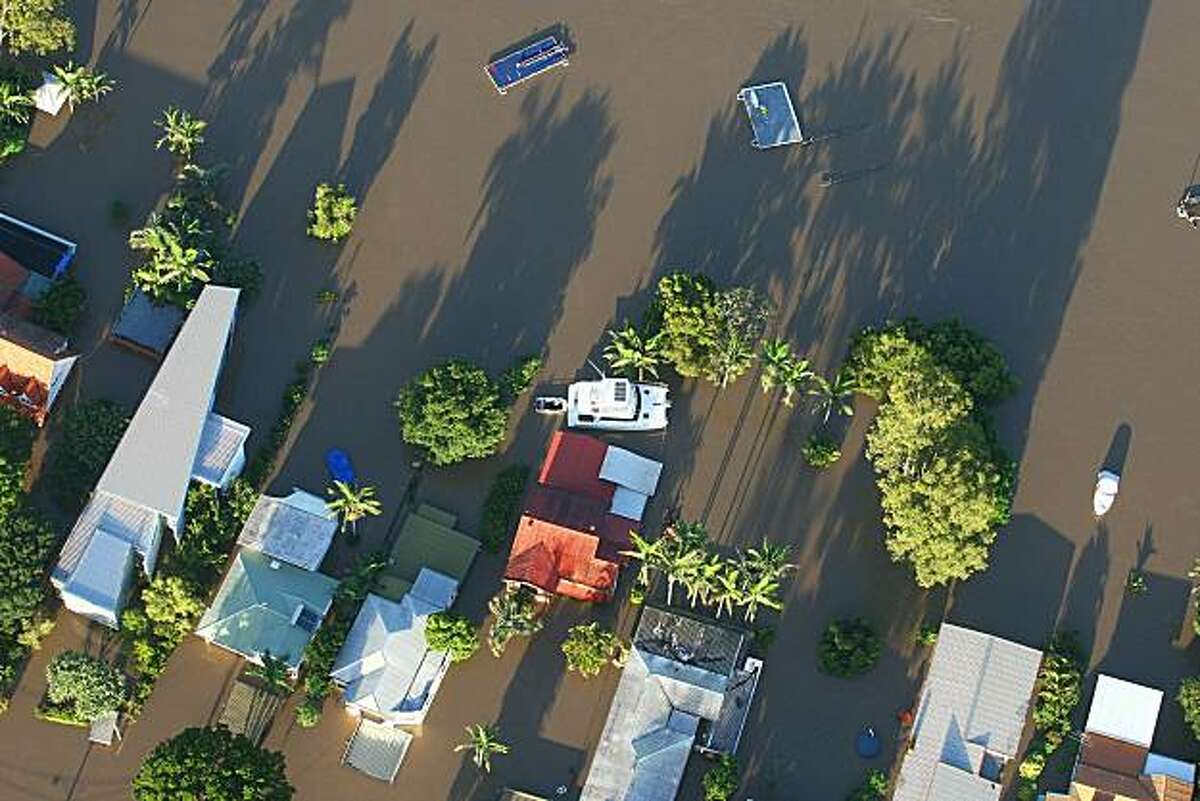 BRISBANE, AUSTRALIA - JANUARY 13: An aerial view of a flooded suburban area adjacent to the Brisbane River on January 13, 2011 in Brisbane, Australia. Twelve people have been confirmed dead in towns in the Lockyer Valley and many more are reported missing after devastating floods inundated the region. Evacuations are underway in several towns and suburbs in and around Brisbane with residents and emergency services preparing the worst floods in over 100 years.