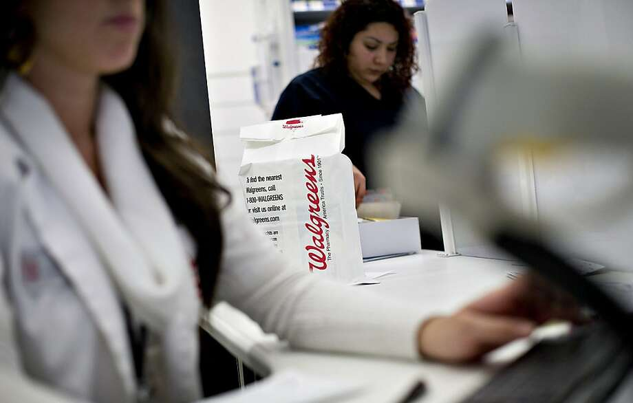 Pharmacist Tzofit Moskovich, left, works at a computer station as Michelle Sorto, a senior pharmacy technician for Walgreen Co., sorts files at a store in Oak Park, Illinois, U.S., on Tuesday, Dec. 20, 2011. Walgreen Co. is scheduled to release earnings data on Dec. 21. Photo: Daniel Acker, Bloomberg