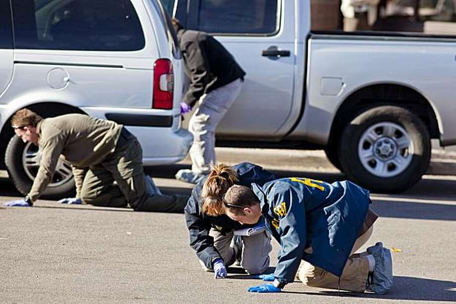 FBI agents and Tucson area law enforcement officers scour the parking lot of the Safeway  in Tucson, Ariz., looking for evidence of Saturday's shootings Monday, Jan. 10, 2011. Two days after a mass shooting at the Safeway, the grocery store is closed andthe parking lot a scene of intense law enforcement activity. Photo: Jack Kurtz, AP