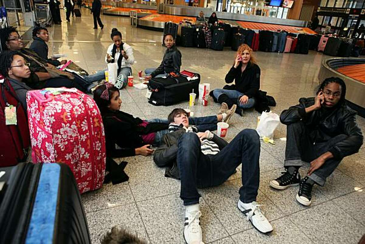 ATLANTA, GA - JANUARY 10: Headed to a convention in California, students from Barbizon Modeling School in Atlanta, including (front left to right) Luisa Restrepo, Brian Welch and Jeremiah Davison, relax in the baggage claim area of Atlanta Hartsfield-Jackson International Airport after a snow storm on January 10, 2011 in Atlanta, Georgia. Atlanta Mayor Kasim Reed and Georgia Governor Sonny Perdue declared a state of emergency because of snowfall and ice across Atlanta and Georgia. A winter storm stretched across the Southeast as freezing rain and sleet followed on the heels of a heavy snow that blanketed the region. The students from Barbizon had all their possible flights cancelled to Los Angeles and had been at the airport for the last 24 hours waiti