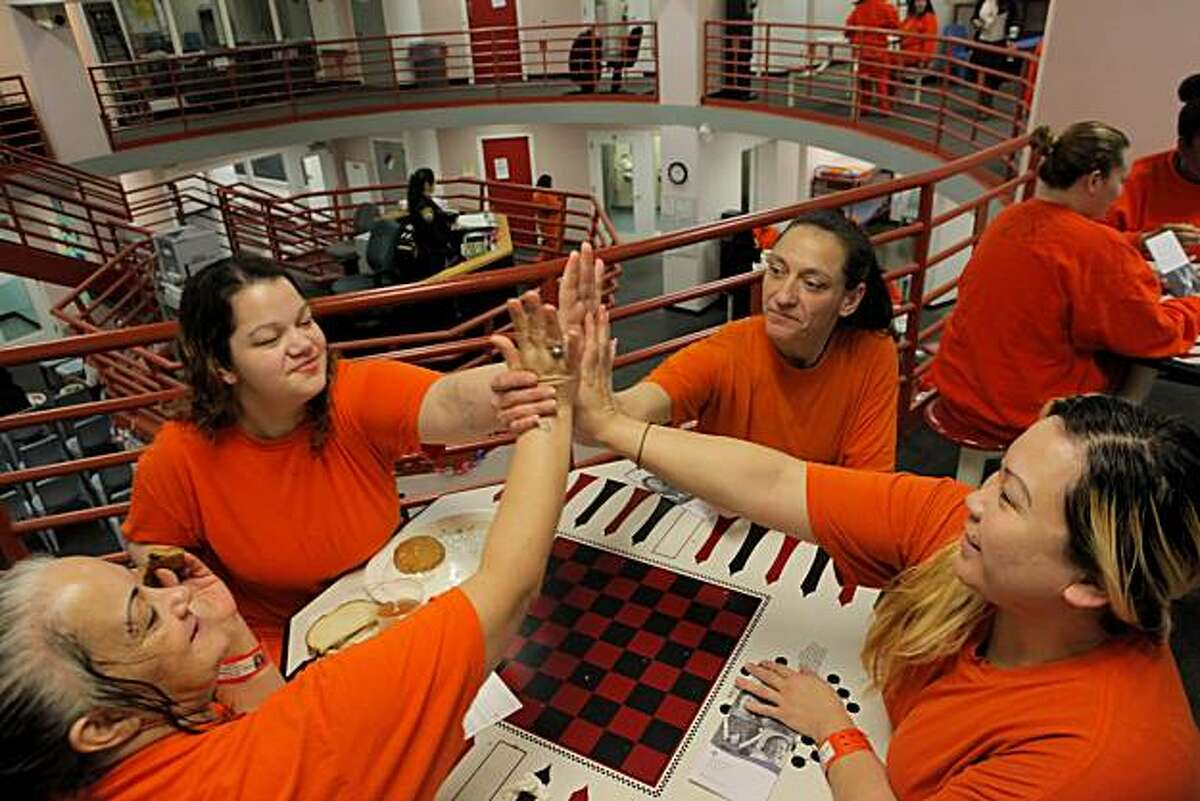 Inmates Rose Olsen, left, Sara Monteverde, Shirin Mizani and Lillian Graham give a high five shake during lunch, Tuesday Dec. 28, 2010, at the San Francisco County Jail in San Francisco, Calif. The women from the sisters program felt good about hearing upon release they will be given free mammograms and follow-up care by the California Pacific Medical Center.
