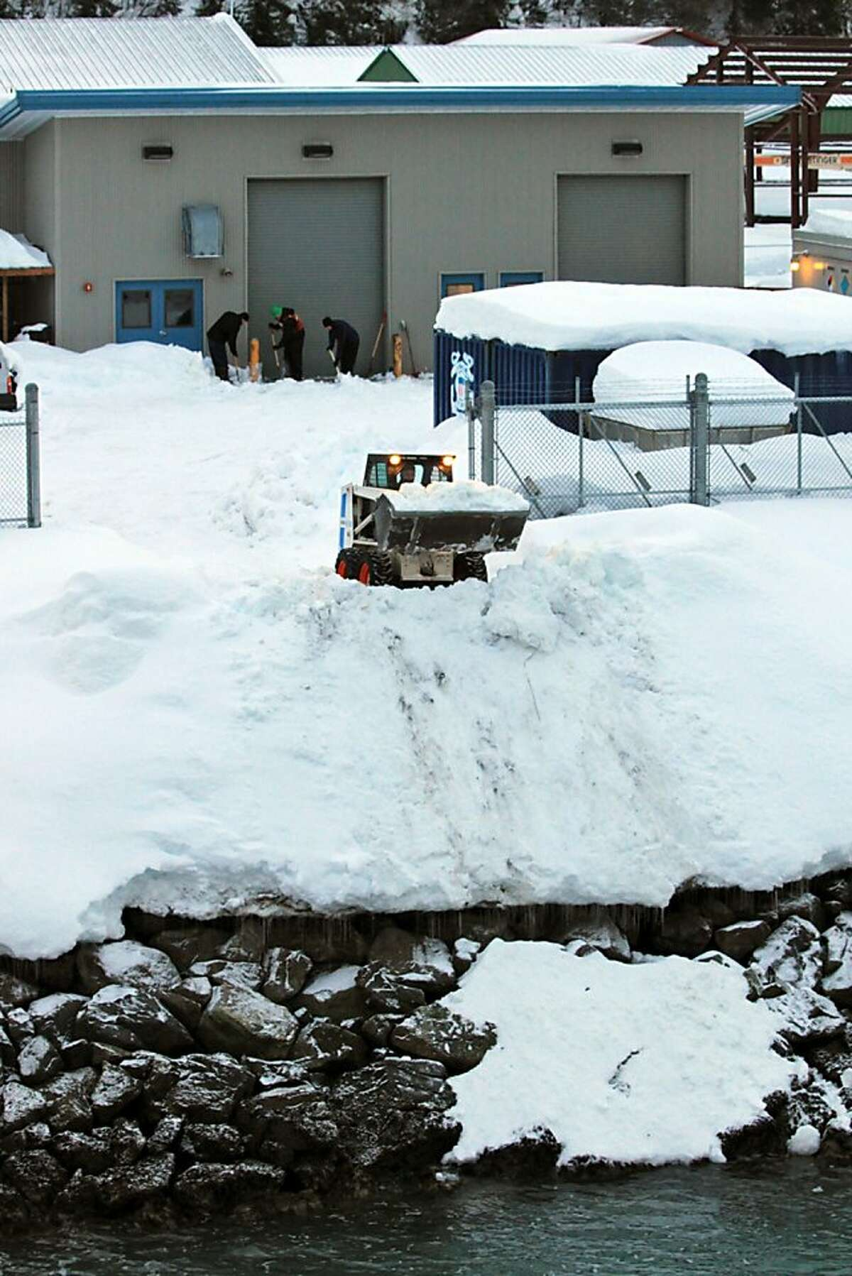 This US Coast Guard photo obtained January 11, 2012 shows the crew of the Coast Guard Cutter Sycamore as they shovel several feet of snow from piers in the Cordova harbor on January 9, 2012. Winter storms over the last three weeks have deposited enough snow in the city of Cordova to damage houses and keep Coast Guard crews shoveling daily to keep the cutter and facility clear and ready for response. AFP PHOTO/US COAST GUARD