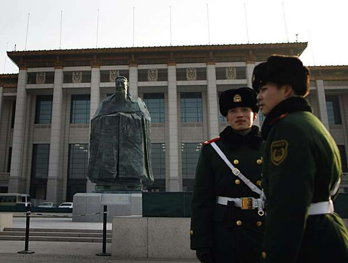 In this Wednesday, Jan. 12, 2011 photo, Chinese paramilitary policemen stands guard in front of a sculpture of the ancient philosopher Confucius on displayed in near the Tiananmen Square in Beijing, China's capital. The mammoth sculpture of Confucius wasunveiled this week off one side of the giant plaza, the political heart of China. It's a curious juxtaposition for a site that's heavy with Communist history _ Mao's body is interred in the middle of it and his giant portrait hangs at one end.