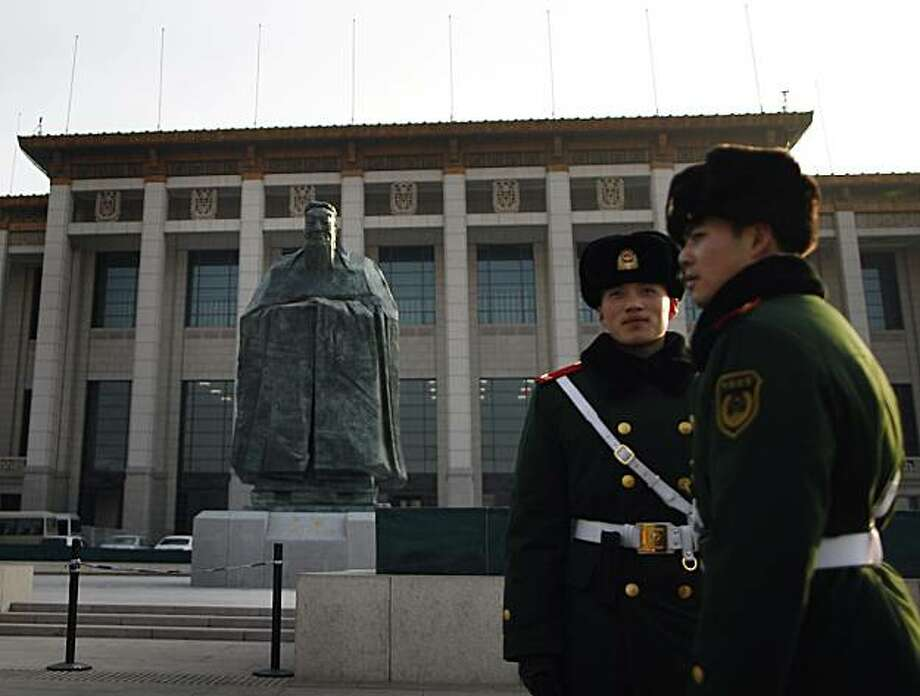 In this Wednesday, Jan. 12, 2011 photo, Chinese paramilitary policemen stands guard in front of a sculpture of the ancient philosopher Confucius on displayed in near the Tiananmen Square in Beijing, China's capital. The mammoth sculpture of Confucius wasunveiled this week off one side of the giant plaza, the political heart of China. It's a curious juxtaposition for a site that's heavy with Communist history _ Mao's body is interred in the middle of it and his giant portrait hangs at one end. Photo: Andy Wong, AP
