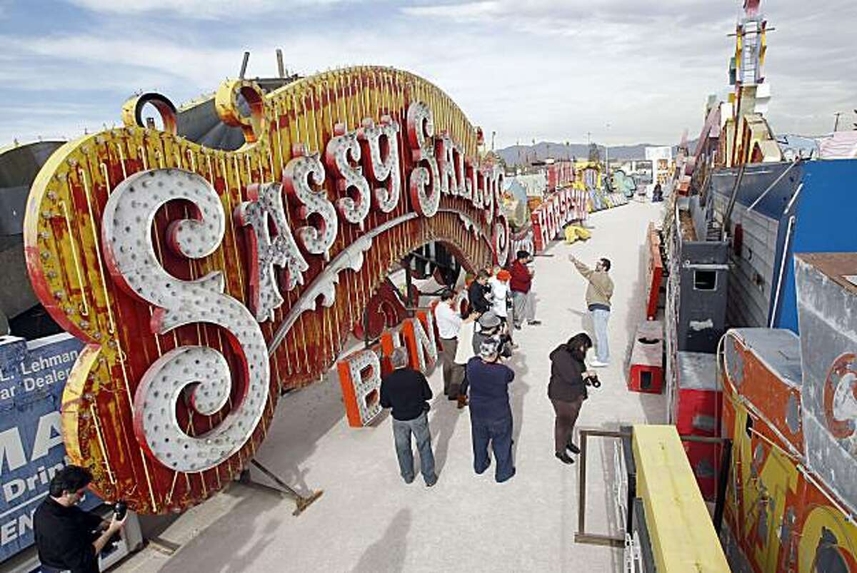 In this photo taken Tuesday, Dec. 14, 2010, tourists navigate a maze of signs that once adorned Las Vegas casinos and business at the Neon Boneyard in Las Vegas. Owners of the collection plan to transform the Boneyard into a museum opening next December.