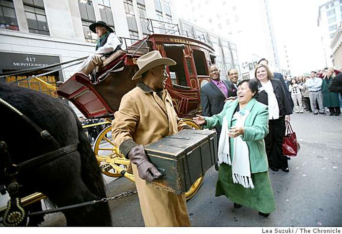 Lovester Law (left) holds the treasure box taken off the Wells Fargo stagecoach after it was driven down Montgomery Street to the Wells Fargo History Museum on Wednesday, December 10, 2008. Pat Correa Director of Go Green (a program under Habitat for Humanity Utah County) shares a laugh with Law as he is transporting the box.