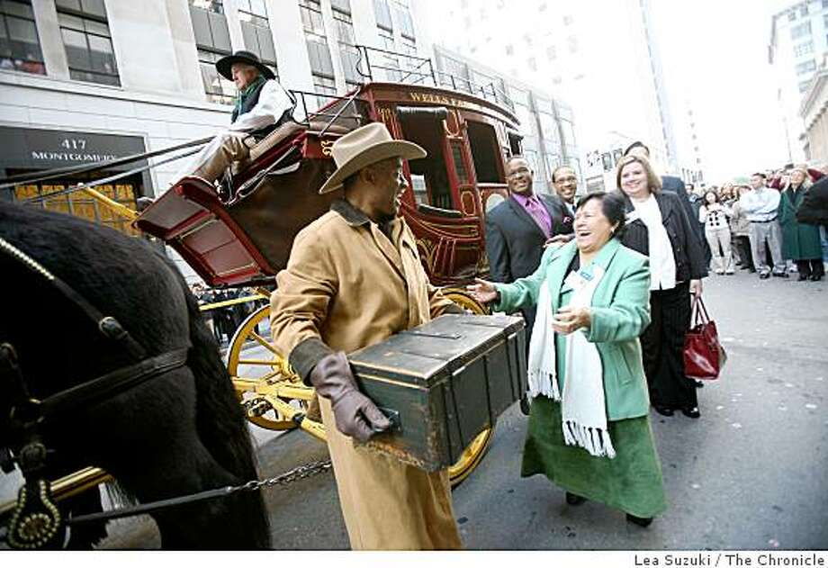 Lovester Law (left) holds the treasure box taken off the Wells Fargo stagecoach after it was driven down Montgomery Street to the Wells Fargo History Museum on Wednesday, December 10, 2008. Pat Correa Director of Go Green (a program under Habitat for Humanity Utah County) shares a laugh with Law as he is transporting the box. Photo: Lea Suzuki, The Chronicle