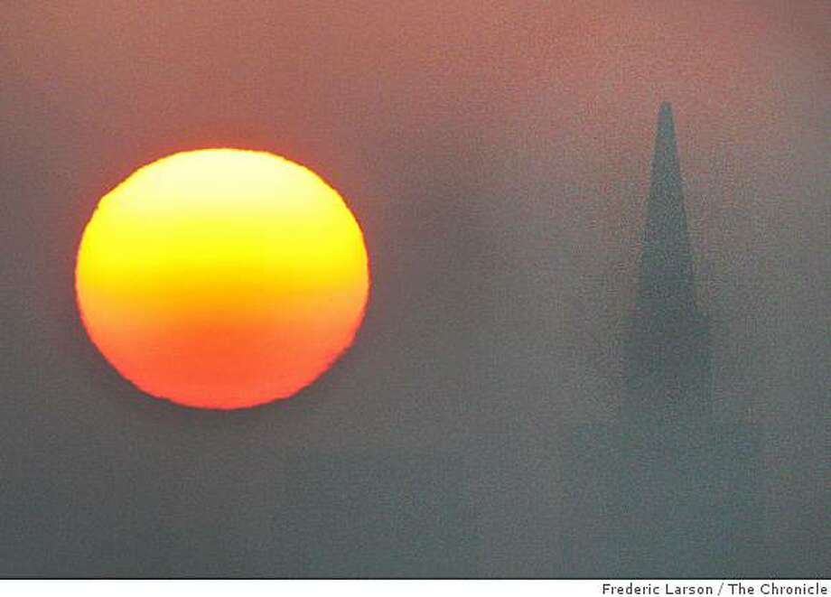 The bright orange fireball appeared out of the haze and light fog this morning on December 12, 2008 from Vista Point lookout on the north side of the Golden Gate Bridge looking towards the Transamerican Pyramid and the San Francisco skyline. Photo: Frederic Larson, The Chronicle