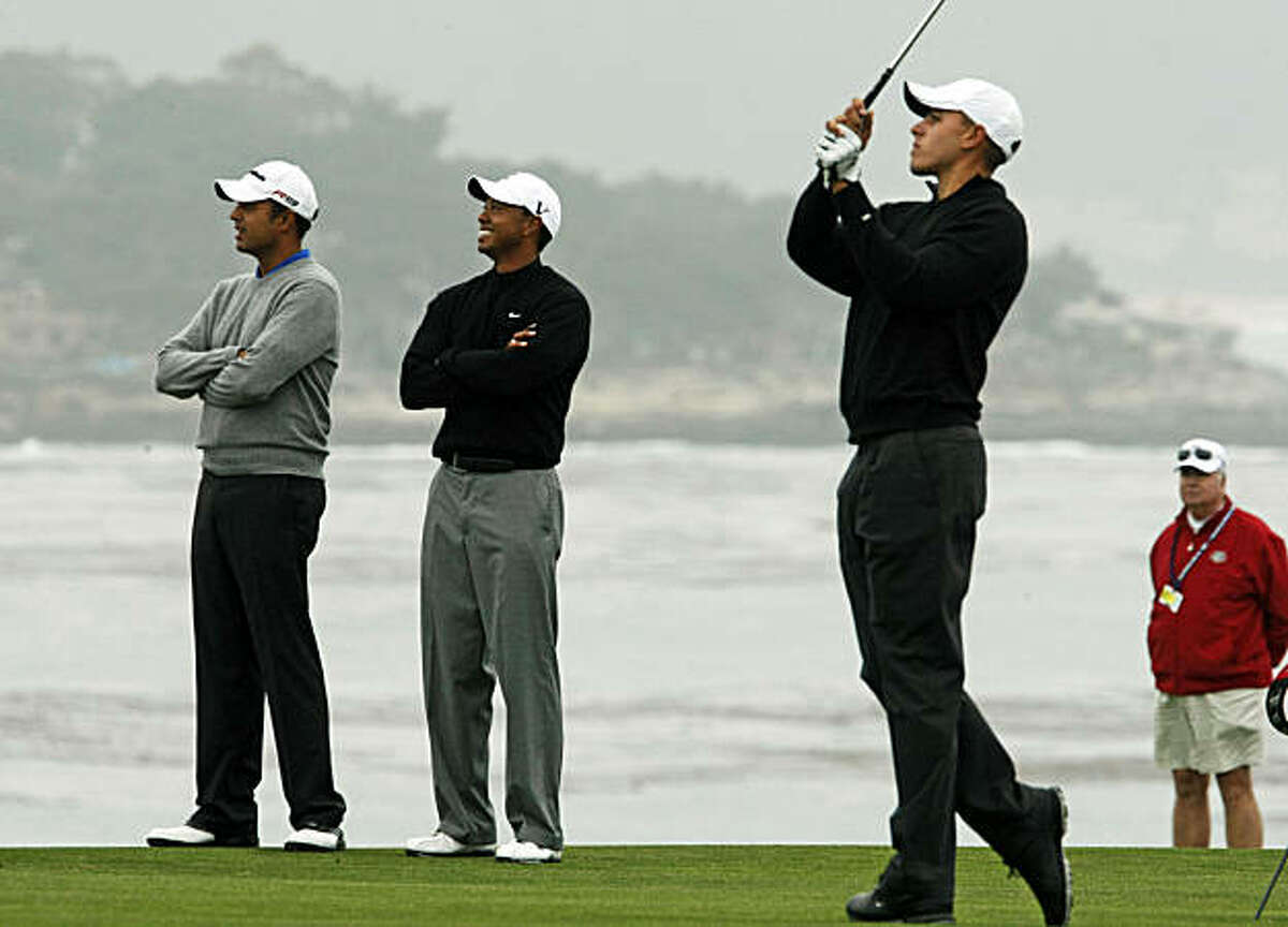 Arjun Atwal and Tiger Woods seem to like amateur-playing partner Joseph Bramlett's approach shot on the 8th hole as practice rounds at the US Open continued Tuesday June 15, 2010 at Pebble Beach Gold Links.