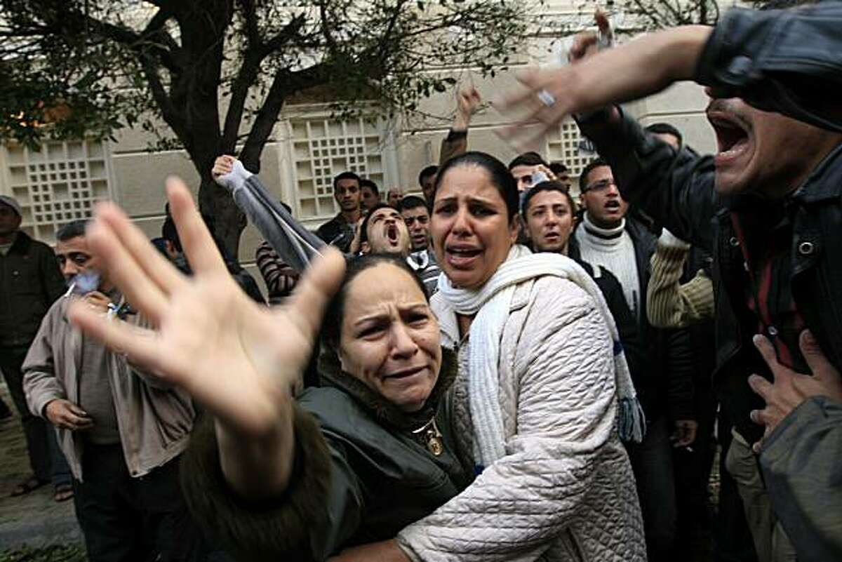 Egyptian Christians mourn outside the Al-Qiddissine (The Saints) church following a midnight mass car bomb attack on the church in the Egyptian port city of Alexandria on January 1, 2011 which killed at least 21, hitting Egypt's Christian community, the biggest in the Middle East.
