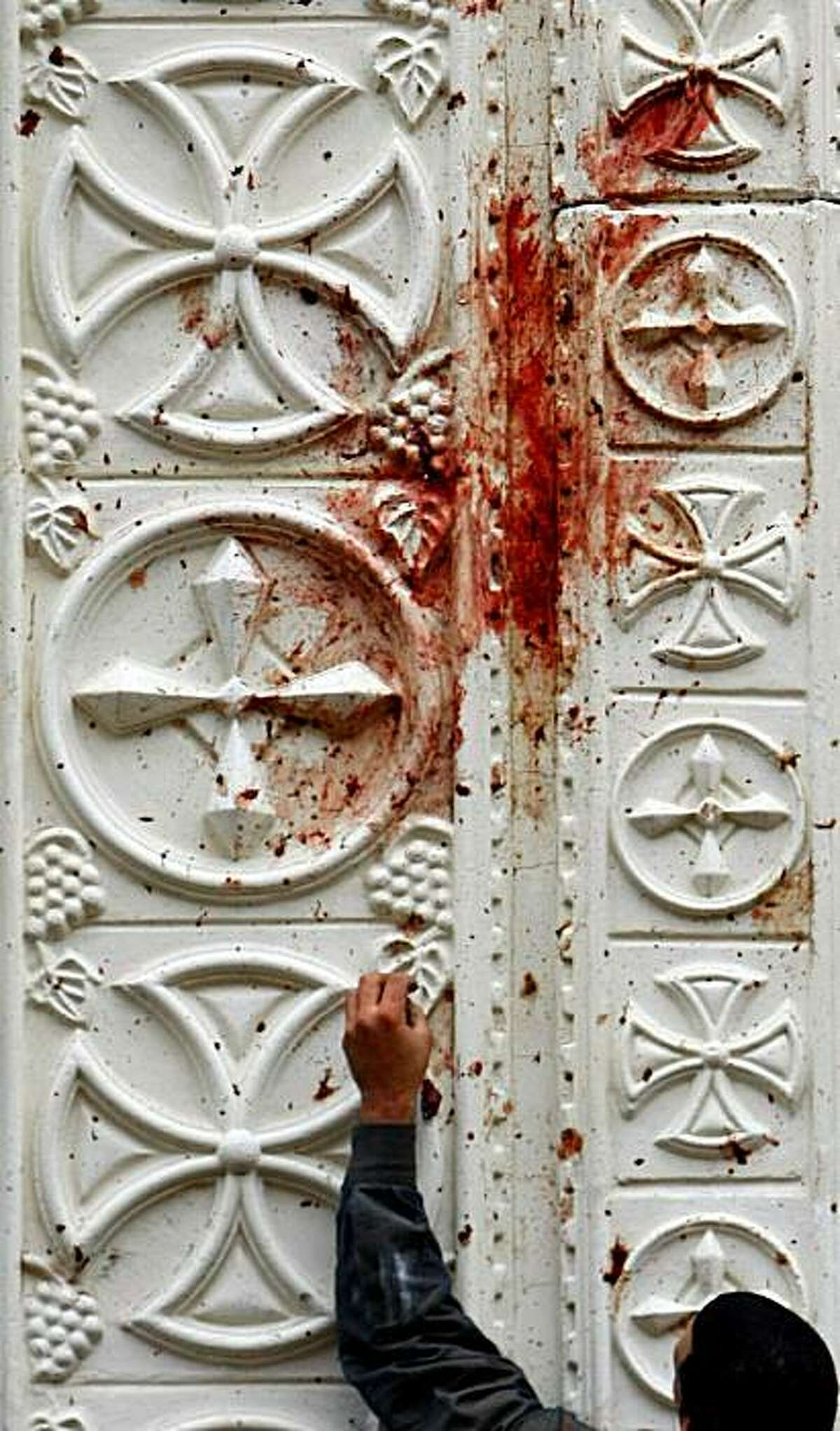 An Egyptian man cleans blood stains from the main gate of the Al-Qiddissine (The Saints) church following an overnight car bomb attack that targeted the church in the Egyptian port city of Alexandria on January 1, 2011 and killed at least 21, hitting Egypt's Christian community, the biggest in the Middle East.