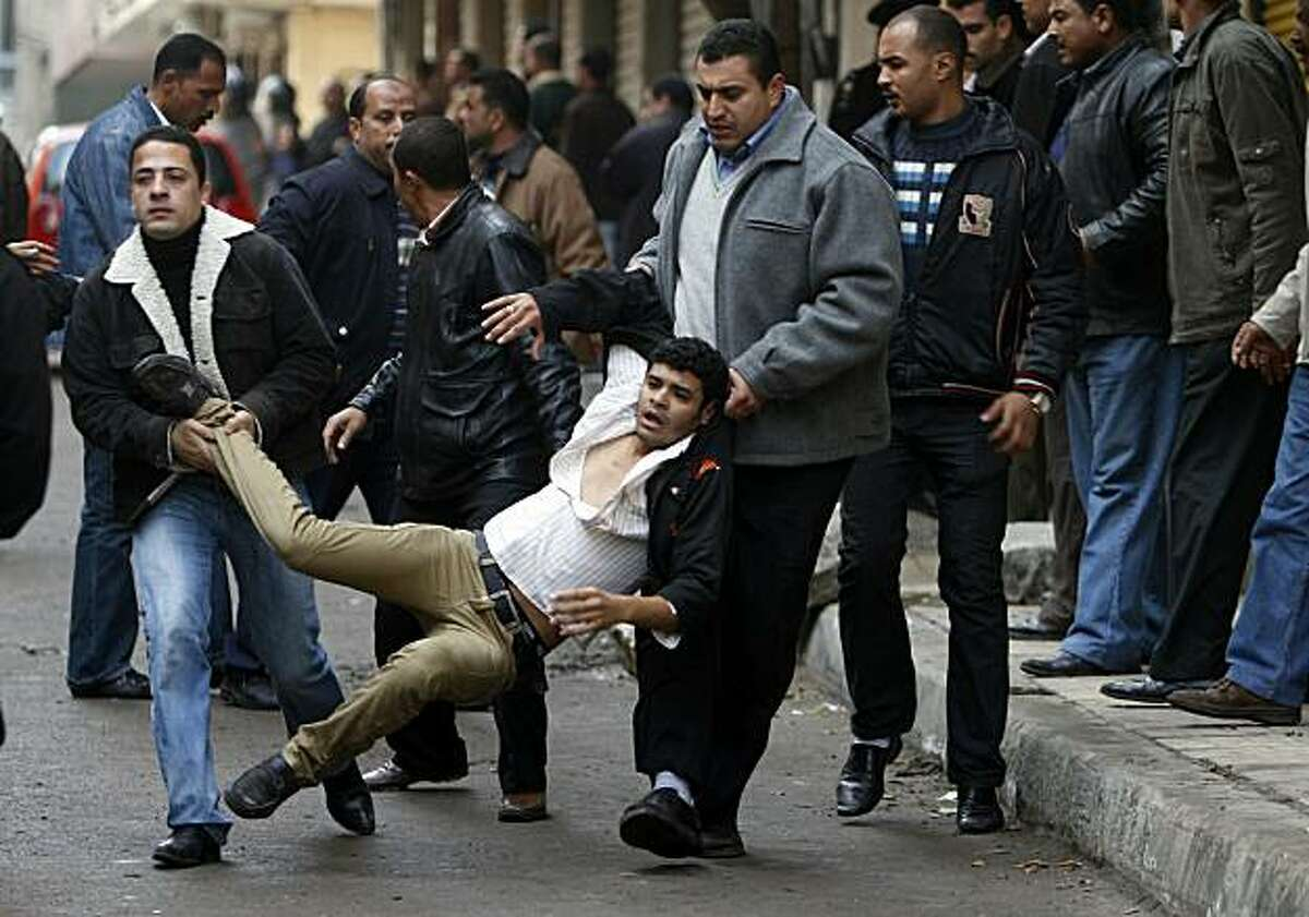 Egyptian policemen in plain clothes detain a Christian youth throwing stones at riot policemen during clashes on January 1, 2011 outside the Al-Qiddissine (The Saints) church following an overnight car bomb attack on the church in the Mediterranean port city of Alexandria in which 21 people people were killed, hitting Egypt's Christian community, the biggest in the Middle East.