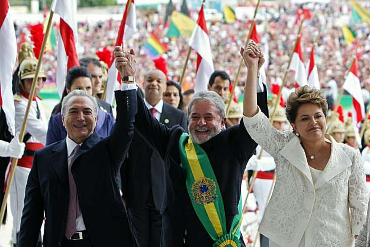 Newly sworn in Brazilian President Dilma Rousseff (R), her Vice Presidente Michel Temer (L) and Brazilian outgoing President Luiz Inacio Lula da Silva raise their hands during the inauguration at Planalto Palace in Brasilia, on January 1, 2011.
