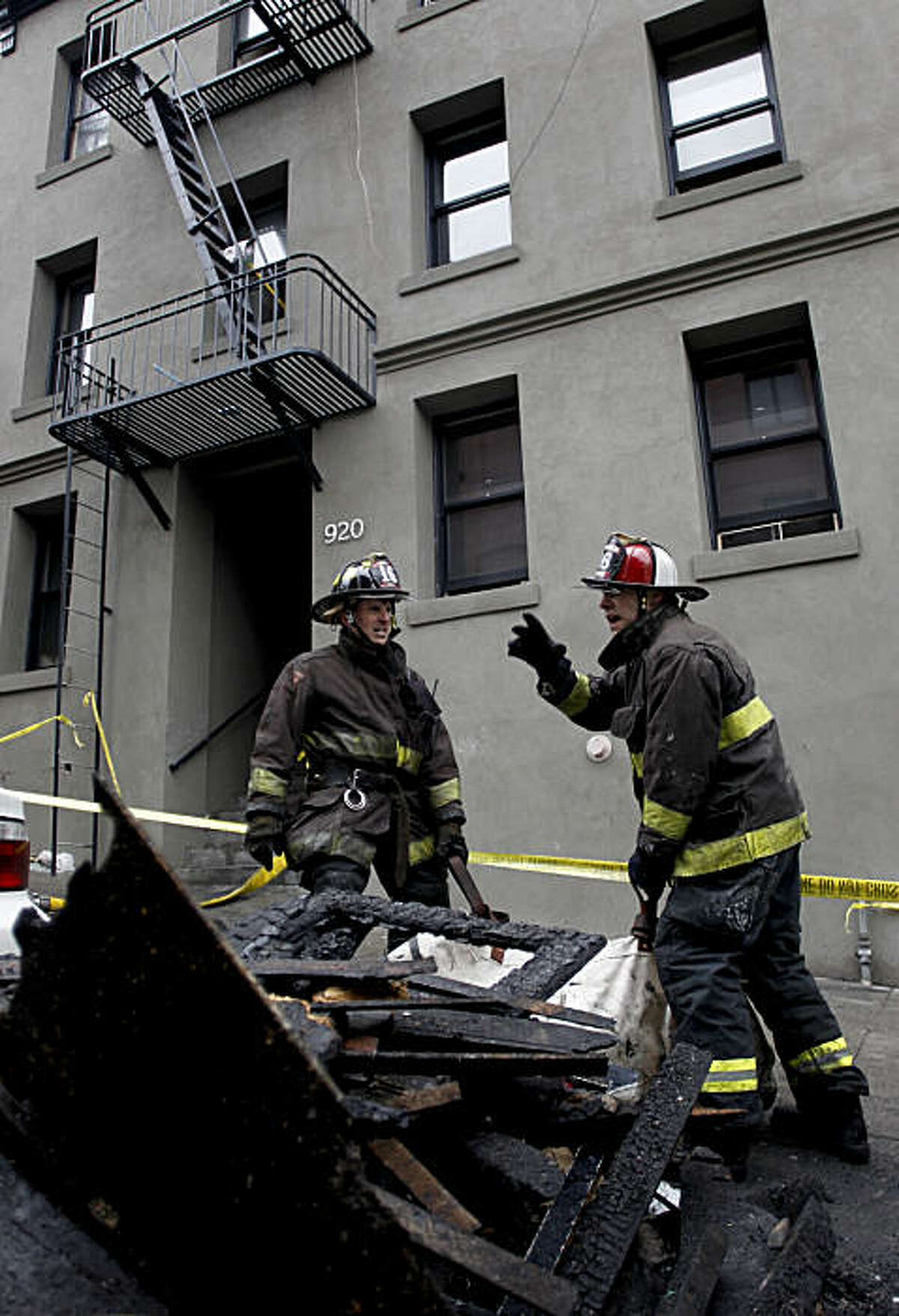 San Francisco firefighters, Rock Plychik, (left) and Pat Steele of Truck 16, remove debris from the burned building, after an early morning fire forced about 45 people from their apartment complex at 920 Montgomery Street, Calif. on Saturday Jan. 1, 2011