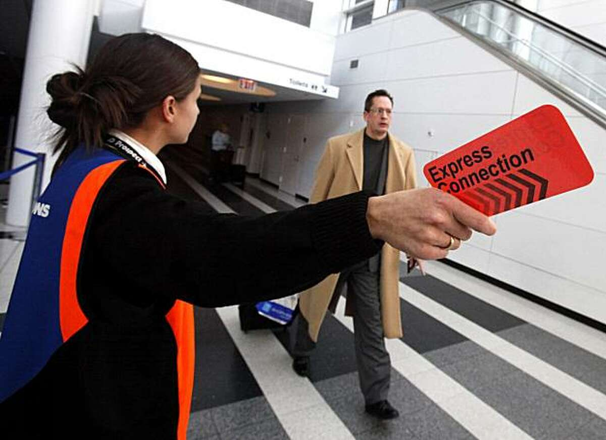 In this Dec. 15, 2010 photo, Iliyana Marinova uses an Express Connection pass to guide a passenger arriving at the International terminal at O'Hare International Airport in Chicago. At Chicago's O'Hare International Airport, one of the world's busiest hubs, federal authorities are using new procedures to help travelers through customs quickly. Airlines that see a plane is late find passengers who will have less than 90 minutes to make a connection and give them bright-orange cards that let them cut to the short, fast-moving customs lines.