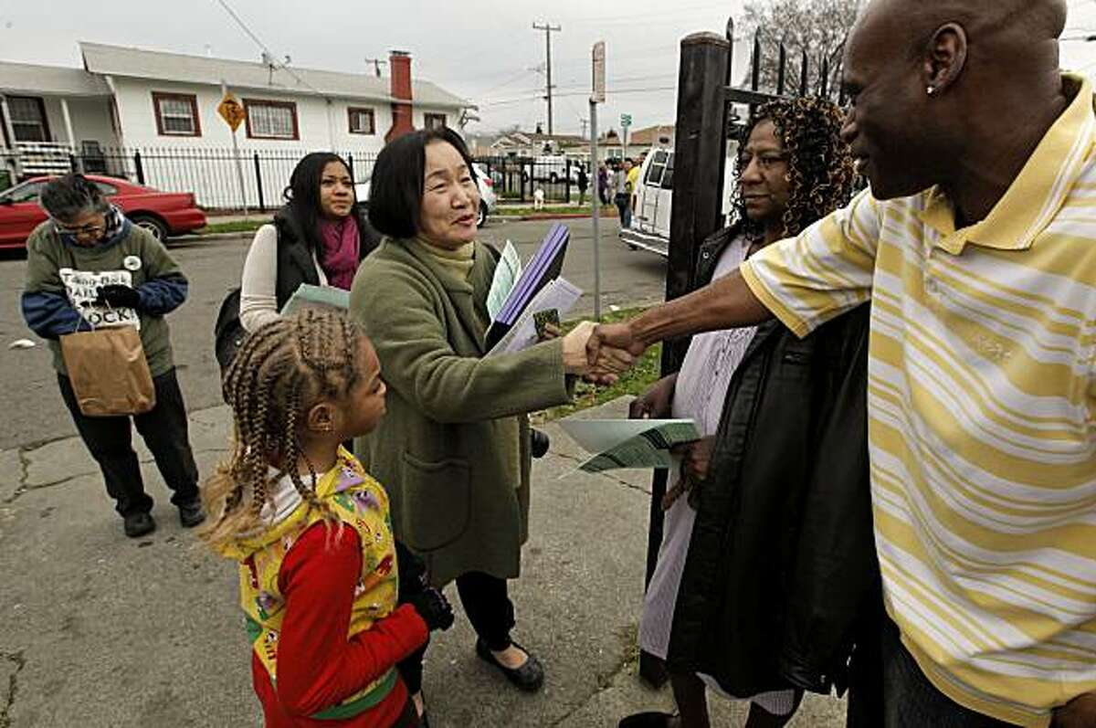 Oakland's new Mayor Jean Quan, greets Derreck Alexander, Alice Prentice and 7-year-old Angelique Turner along D Street as she canvases the Beat 33x neighborhood, of East Oakland, Calif. on Saturday Jan. 8, 2010, speaking with residents, passing out leaflets and trying to organize an effort to improve the area.