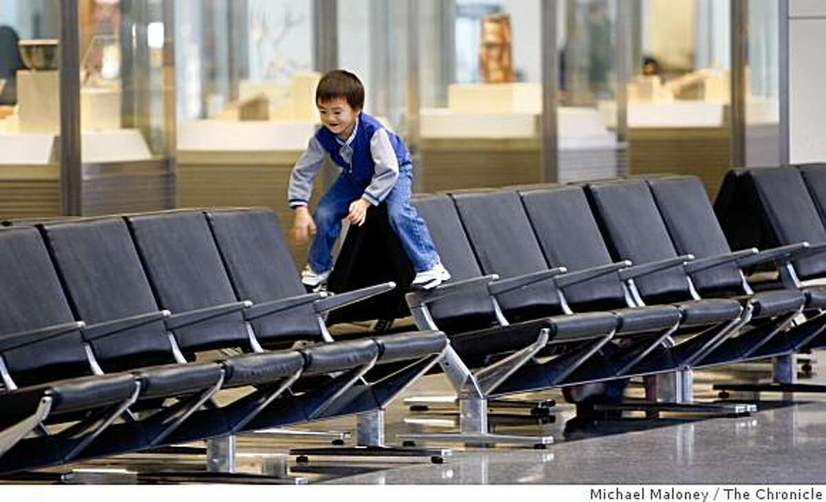 Six year old Matthew Kuo of Sunnyvale, along with his younger sister Tiffany (not seen) play on the empty seats in the International Terminal at the San Francisco International Airport on a quiet day before Thanksgiving, Wednesday, November 26, 2008.