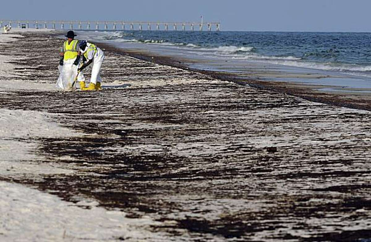FILE - In a June 23, 2010 file photo, crews work to clean up oil from the Deepwater Horizon oil spill washed ashore at Pensacola Beach in Pensacola Fla. As the Gulf oil spill gushed out of control this summer, BP's financial liabilities expanded so rapidly that experts wondered if the company had drilled its last well. Only months later, though, the British oil giant has pulled itself back from the brink.