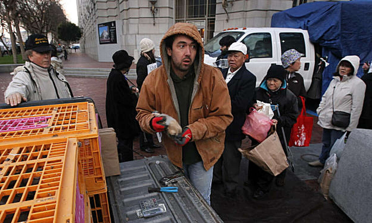 Poultry vendor Jayce Benton preps a game bird for customers lined up at the Civic Center farmers' market in San Francisco, Calif., on Wednesday, Jan. 5, 2011. Animal rights activists have been protesting alleged mistreatment of the birds, which have been sold at the market for several years, since last April. Vendors say they have complied with all ordinances.