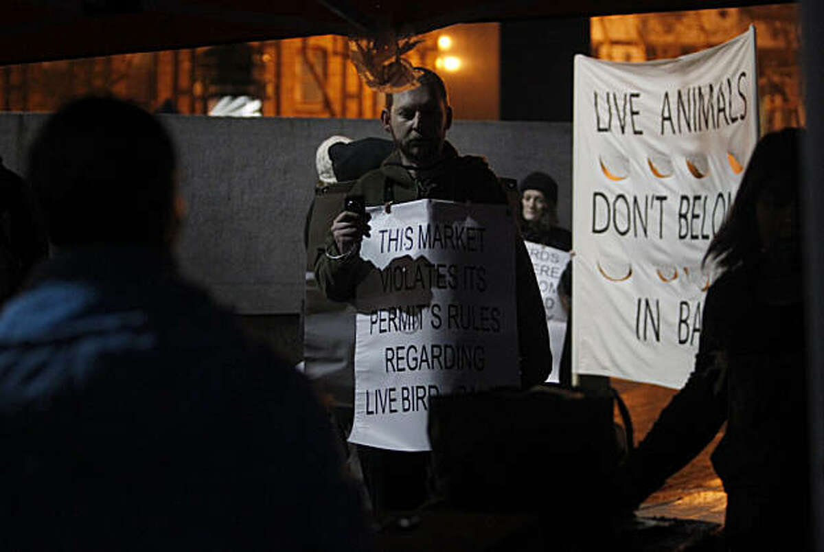 Andrew Zollman and other protesters monitor the activity of a vendor (foreground) selling live poultry at the Civic Center farmers' market in San Francisco, Calif., on Wednesday, Jan. 5, 2011. Animal rights activists have been protesting alleged mistreatment of the birds, which have been sold at the market for several years, since last April. Vendors say they have complied with all ordinances.