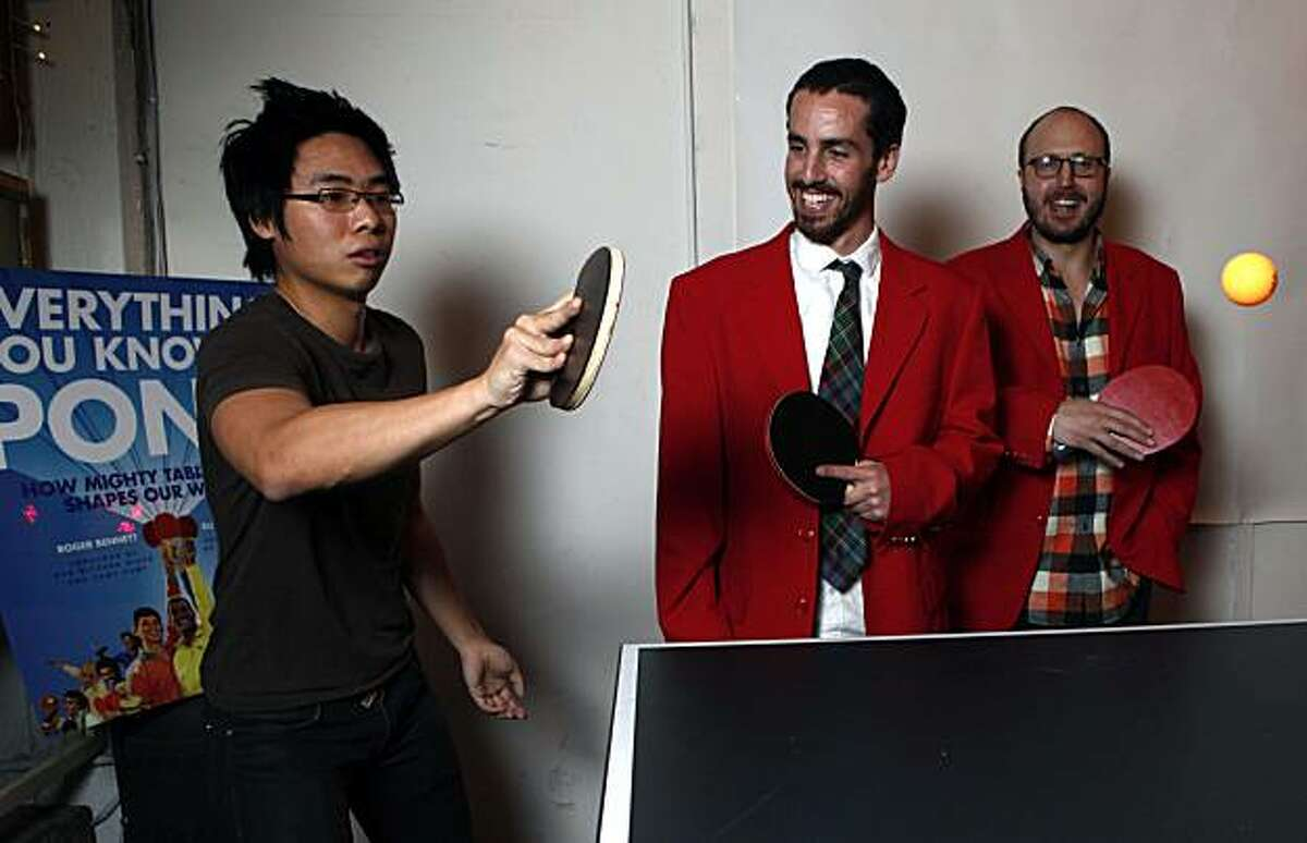 Eli Horowitz center, and Roger Bennett right, look on as James Yu plays a game of table tennis at Capp Street Reserve in San Francisco. Horowitz and Bennett are co-authors of