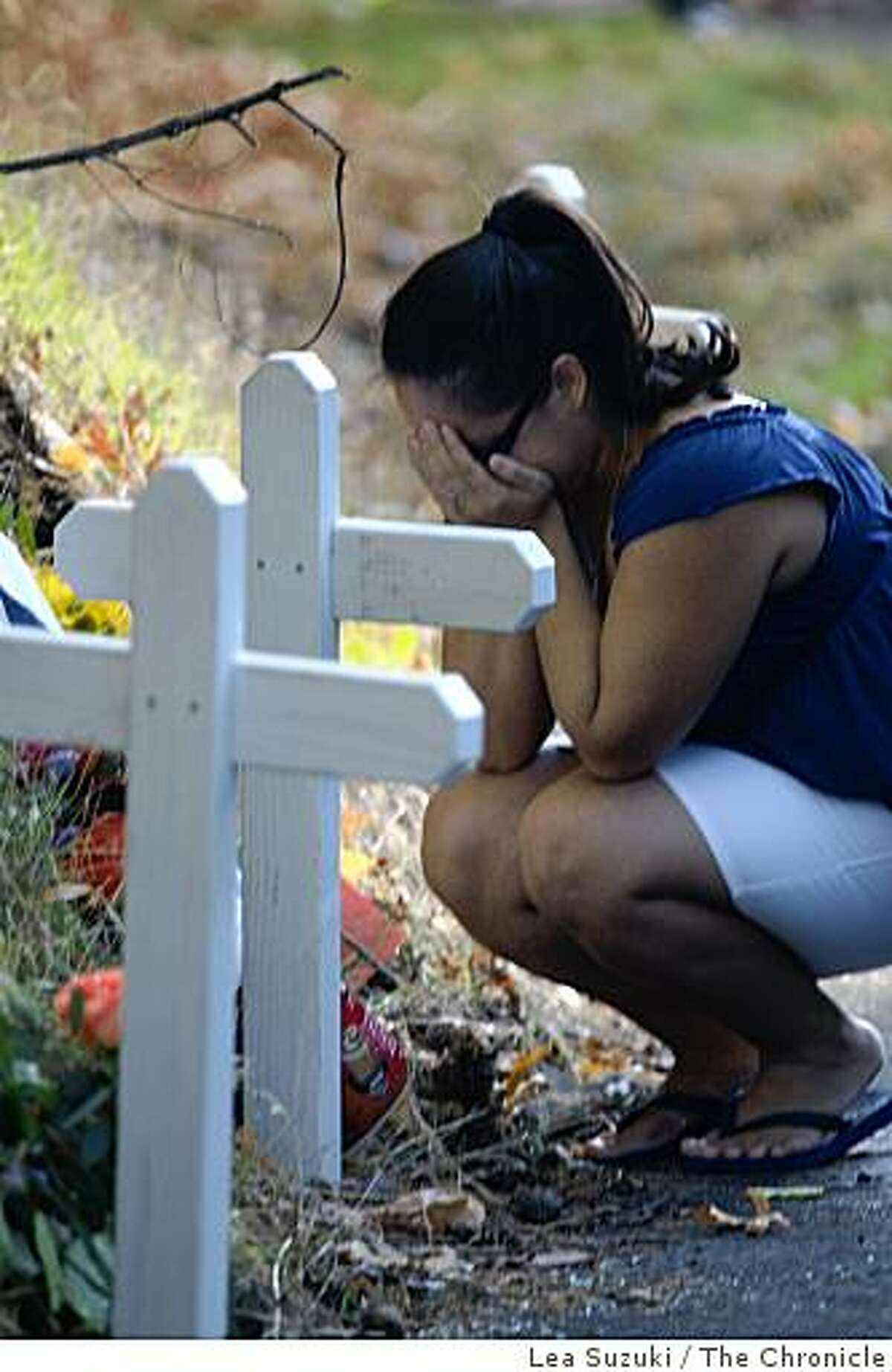 On Sunday, November 16, 2008 near Angwin, Calif. Desiree Quijano, 21, Pacific Union College senior, buries her face in her hands while visiting the makeshift memorial on Deer Park Road where 4 Pacific Union College students were killed in a crash on Saturday evening.