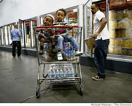 Jonah, left, and Liya get a ride in the grocery cart at the San Francisco Costco as their dad Fasil Fikreab, right, does the family grocery shopping on November 18, 2008. Grocery stores are holding up surprisingly well in this economic downturn.