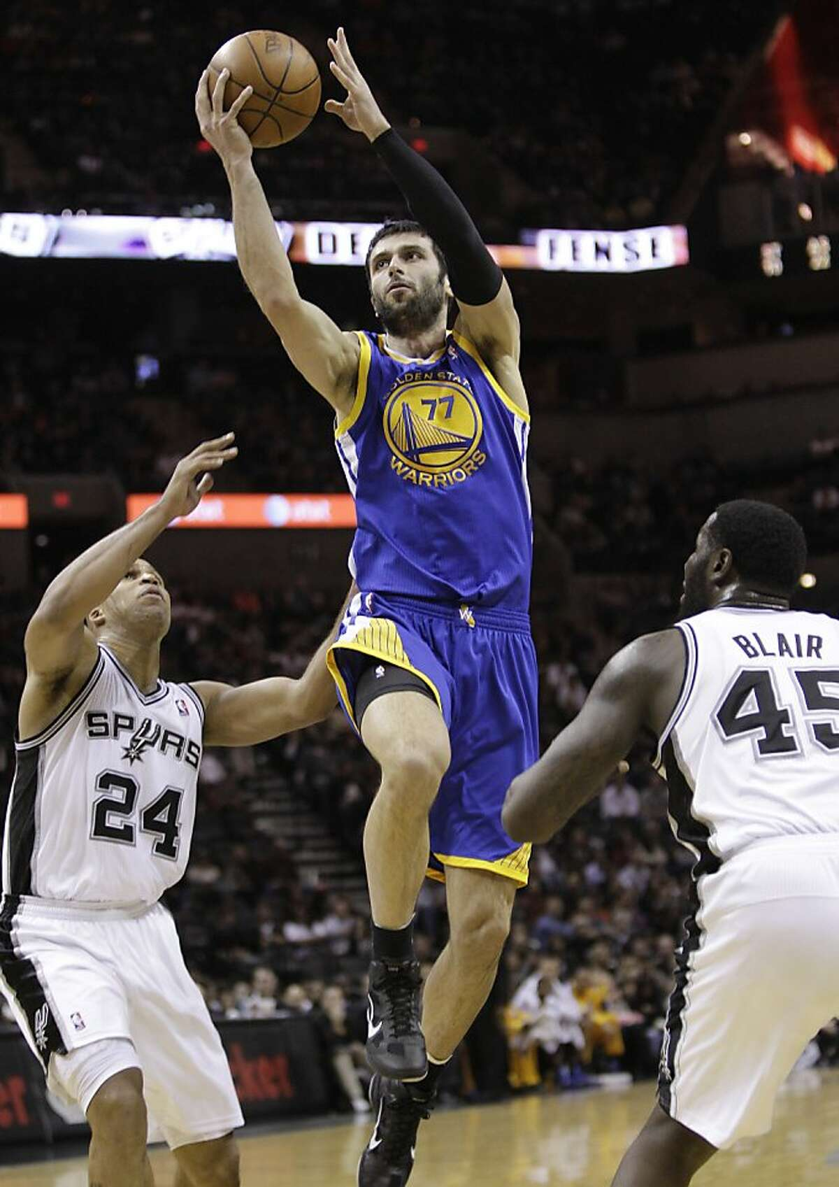 Golden State Warriors' Vladimir Radmanovic (77), of Serbia, drives between San Antonio Spurs' Richard Jefferson (24) and DeJuan Blair during the fourth quarter of an NBA basketball game, Wednesday, Dec. 8, 2010 in San Antonio. The Spurs won 111-94. (AP Photo/Eric Gay)