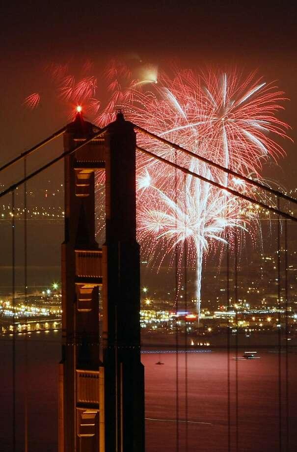 Fireworks illuminate the sky above San Francisco through the Golden Gate Bridge, on July 4, 2009. Photo: Lance Iversen, The Chronicle