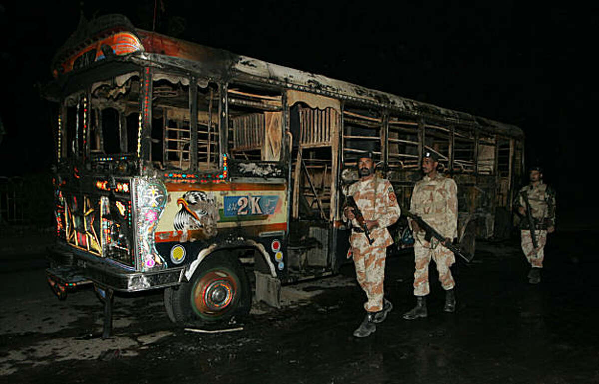 Soldiers of Pakistan's para military force stand guard near a bus burned by angry crowd reacting over the target killing of a worker of Pakistan's ethnic political party Muttahida Qaumi Movement in Karachi, Pakistan on Monday night, Jan. 3, 2011. Pakistan's prime minister tried Monday to keep his ruling coalition in power after a key party MQM said it was defecting to the opposition, leaving the government without majority support in parliament.